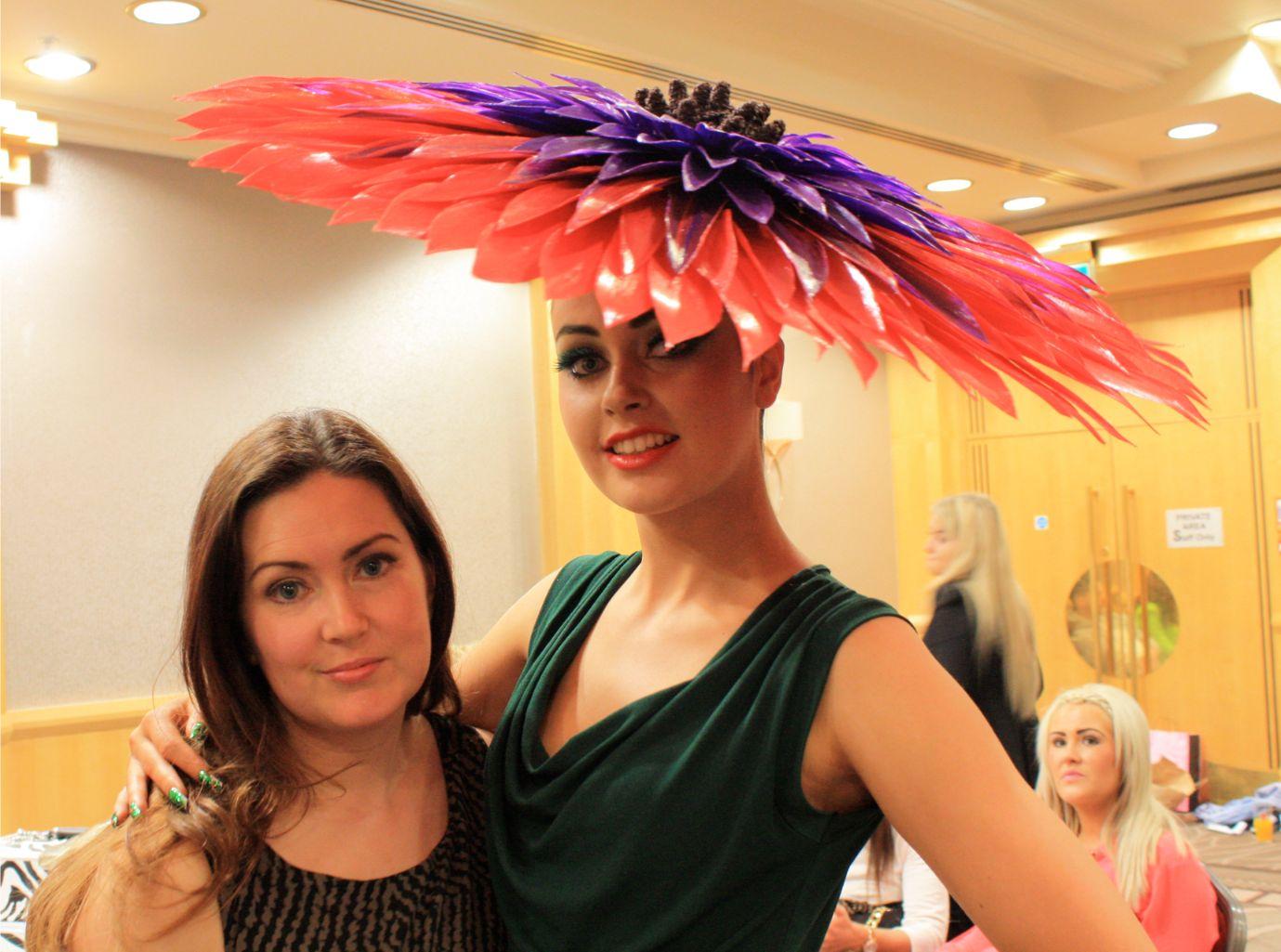 two women, one is wearing big orange and purple flower head piece